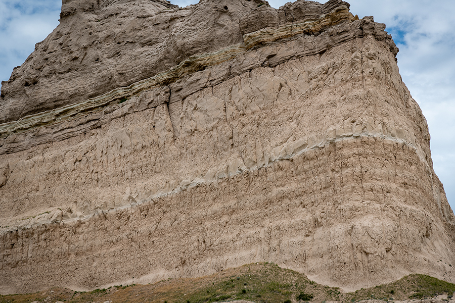 Eagle Rock – This photograph of the midsection of Eagle Rock revels three layers of volcanic ash and silt deposited in western Nebraska by a super violent volcanos between 50 and 31 million years ago.