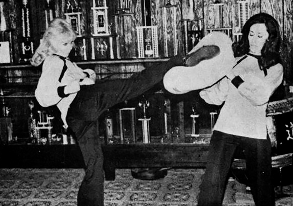 Practice  Karyn Turner practices her kicks with the help of her sensei's wife, Malia Dacascos circa 1980 - Photographer Unknown.